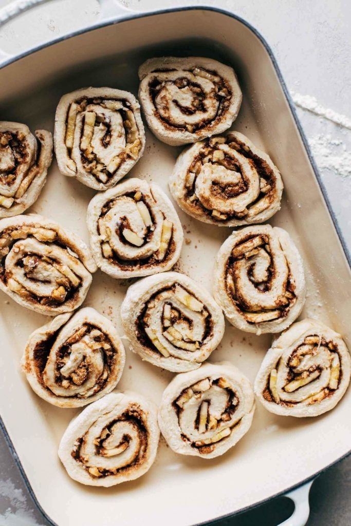sliced cinnamon rolls in a baking pan before proofing