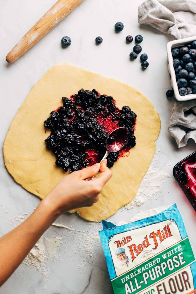 spreading blueberry filling on a rolled out sheet of brioche dough