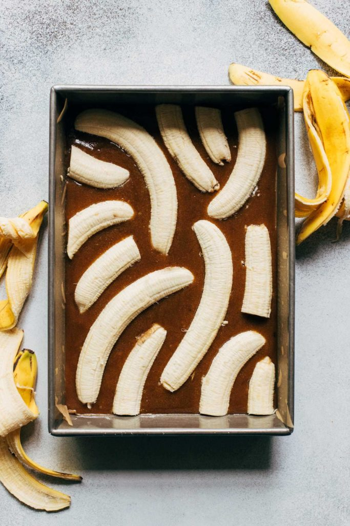 banana slices placed at the bottom of a baking dish with butter and sugar