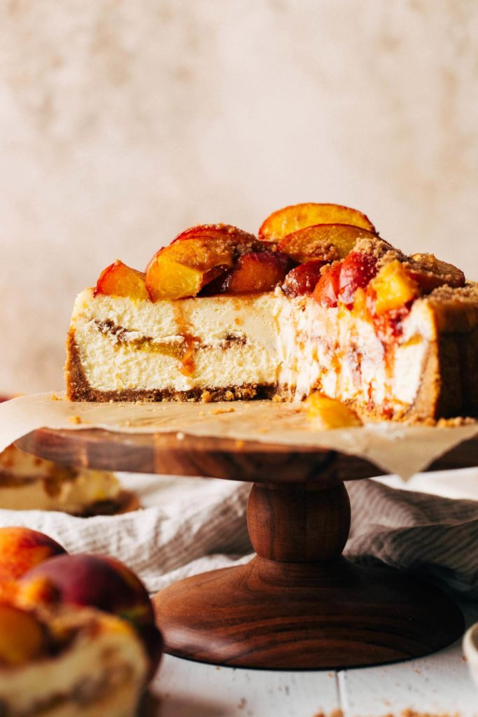 the inside of a sliced peach cobbler cheesecake with peaches baked inside