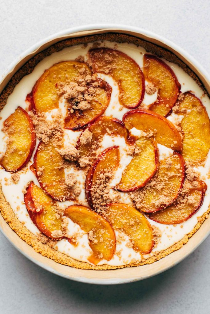 the top view of cheesecake batter half filled in a springform pan with roasted peaches laid on top