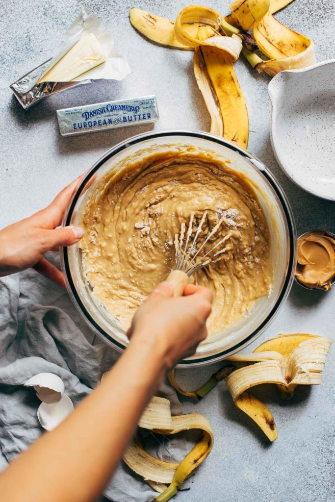 whisking a bowl of peanut butter cake batter