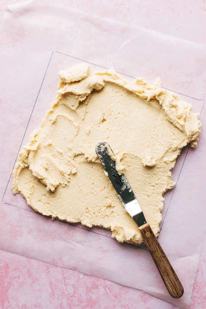 spreading shortbread dough on a sheet of wax paper