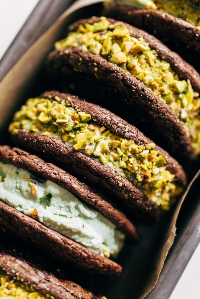 close up on the side of two brownie cookies sandwiched with pistachio ice cream