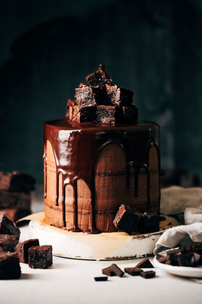 layered brownie cake covered in chocolate frosting, chocolate ganache drip, and a pile of brownies on top