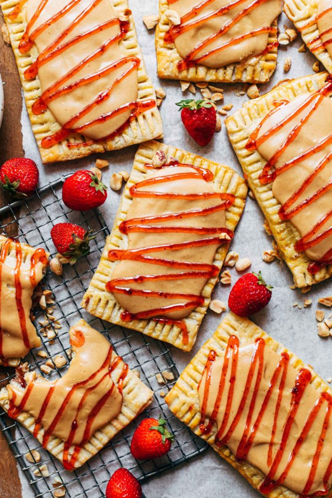 peanut butter and jelly pop tarts scattered on a sheet of parchment paper