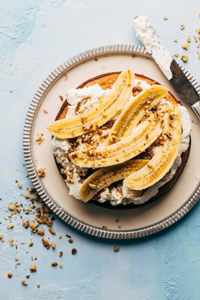 the top of a banana tres leches cake topped with banana slices