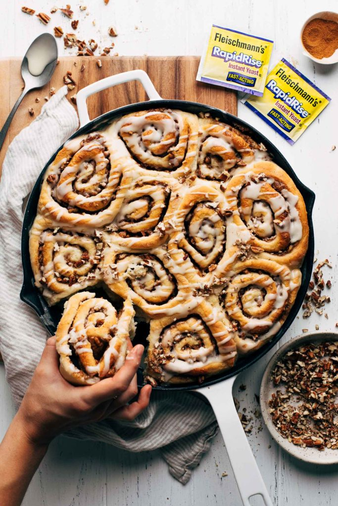 pulling a maple pecan cinnamon roll from the pan