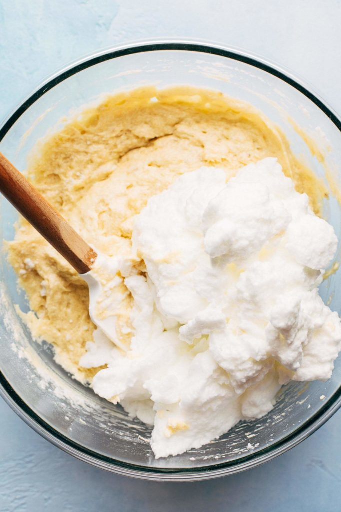 mixing whipped egg whites into a bowl of banana cake batter