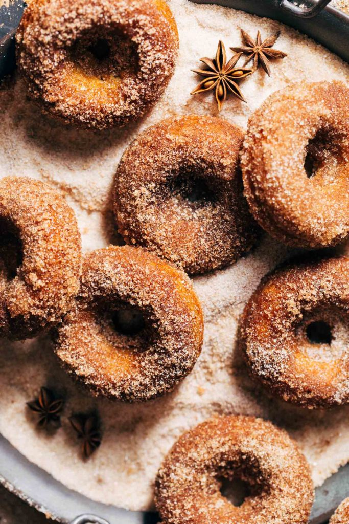 apple cider donuts in a bed of cinnamon sugar